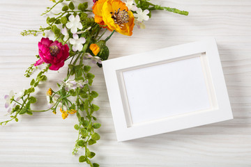 Flower bouquet and a blank white photo frame, copy space, on a white wooden background.