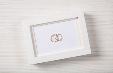 Golden wedding rings on a blank white photo frame, top view, isolated on a white wooden background.