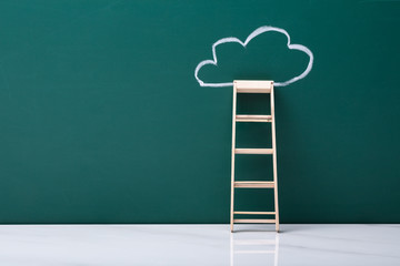 Wooden Ladder Leaning On Green Blackboard