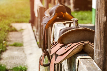 Old horse saddle placed on wooden fence next to house, lit by sun.