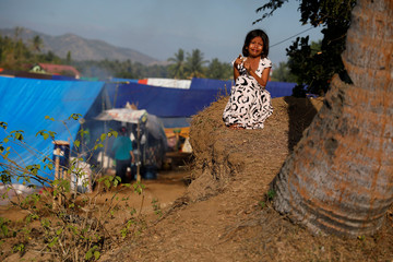 A girl cries as she waits for breakfast at a refugee camp after an earthquake hit on Sunday at Sigar Penjalin village in North Lombok