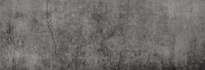 Textur einer fast schwarzen Betonwand mit leichten Rissen in XXL-Größe als Hintergrund, auf die leichtes Licht fällt