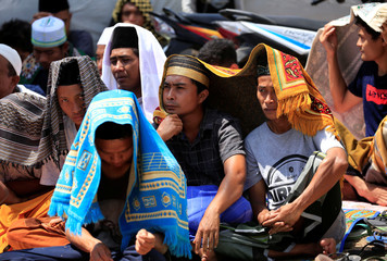Villagers cover their heads as they sit before Friday prayer at a refugee camp after earthquake hit Sigar Penjalin village in North Lombok