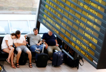 Passengers are seen at terminal A beside board showing cancelled flights during a wider European strike of Ryanair airline crews to protest slow progress in negotiating a collective labour agreement at Schoenefeld airport