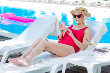 Deck chair. Modern grandmother wearing bright red swimming suit lying on deck chair near outside pool