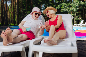 Funny photos. Mature blonde-haired woman wearing red swimming suit showing funny photos her husband