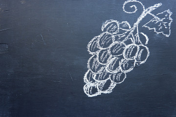 Grapes, drawing chalk on a black wooden board. Crafting a bunch of grapes. Empty place for text.