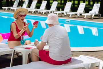 Winning game. Blonde-haired retired woman feeling happy winning card game while playing with husband near pool