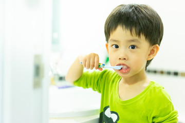 A boy brushes his teeth by himself in the restroom.