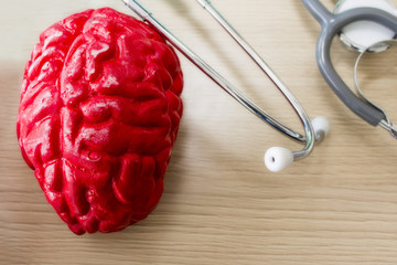 Stethoscope,red brain model and medical equipment on table.Copy space.