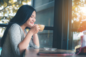 Beautiful attractive young Asian woman holding a cup of coffee or coffe in hand at cafe in the morning, vintage color tone.