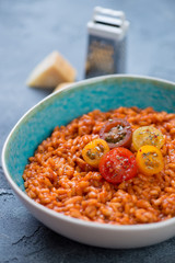 Bowl of tomato risotto topped with fresh sliced tomatoes, vertical shot, closeup