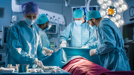 Diverse Team of Professional Surgeons Performing Invasive Surgery on a Patient in the Hospital Operating Room. Nurse Picks Up Instruments, Anesthesiologist Monitors Vitals. Real Modern Hospital.