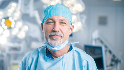 Portrait of the Professional Surgeon Taking off Surgical Mask after Successful Operation. In the Background Modern Hospital Operating Room.