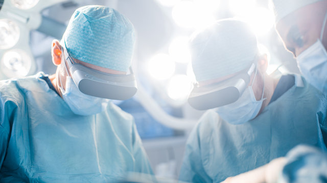 Close-up Shot of a Surgeon Perform State of the Art Surgery in High Tech Hospital using Augmented Reality Glasses. Doctors and Assistants Working in Operating Room.