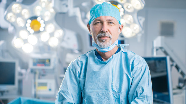 Portrait of the Professional Surgeon Looking Into Camera and Smiling after Successful Operation. In the Background Modern Hospital Operating Room.