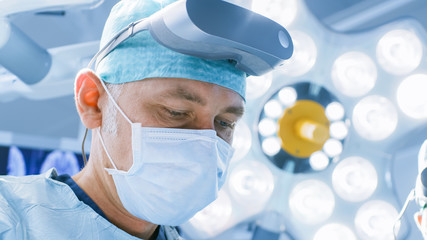 Close-up Shot of a Surgeon with Augmented Reality Glasses Performing State of the Art Surgery in High Tech Hospital. Doctors and Assistants Working in Operating Room.