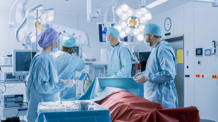 Diverse Team of Professional surgeon, Assistants and Nurses Performing Invasive Surgery on a Patient in the Hospital Operating Room. Surgeons Talk and Use Instruments. Real Modern Hospital