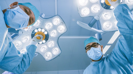 Low Angle Shot POV Patient View: Two Professional Surgeons Turning on Surgery Lights while Bending over Patient.
