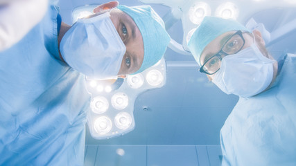 Low Angle Shot POV Patient View: Two Professional Surgeons Holding Surgical Instruments Starting Surgery.