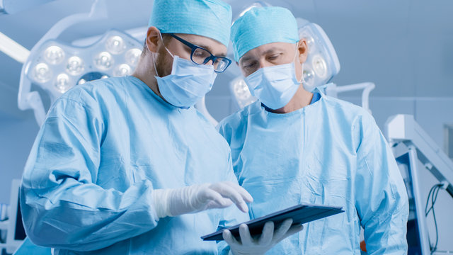 Two Professional Surgeons Use Digital Tablet Computer while Standing in the Modern Hospital Operating Room.