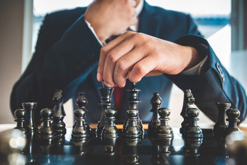 hand of businessman moving chess figure in competition success play. strategy, management or leadership concept