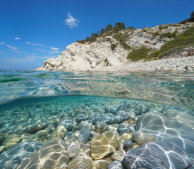 Foto op Canvas Kust Cove on rocky coast with pebbles and rocks underwater, split view above and below water surface, Mediterranean sea, Cala del Frances, Costa Blanca, Javea, Alicante, Valencia, Spain