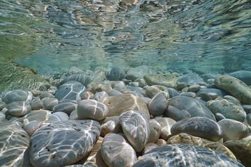 Pebbles and rocks below water surface in shallow water in the Mediterranean sea, underwater scene, Javea , Alicante, Valencia, Spain