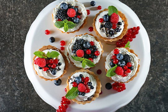 Tasty tartlets with whipped cream and berries on dessert stand, top view