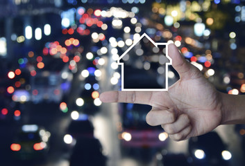 House icon with copy space on finger over blur colorful night light city with cars, Business real estate communication concept