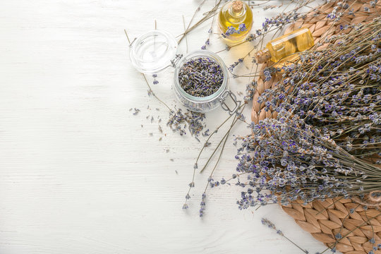 Beautiful lavender flowers with bottles of essential oil on white table