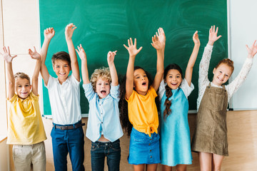 adorable happy schoolchildren with raised hands standing in front of blank chalkboard