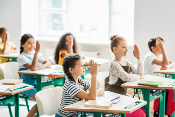 group of classmates raising hands to answer question during lesson