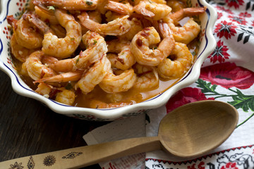 Appetizing shrimps baked with spicy sauce and spices and butter in ceramic ware are served to the table