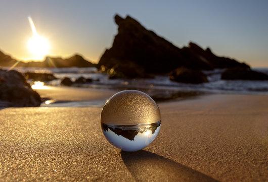 Glass ball on Burgess Beach at sunrise