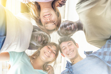 Upward view of five multi ethnic teenagers looking down, sun rays coming from behind