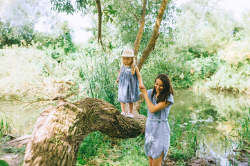 mother holding hands with daughter and helping her to walk on tree trunk, with lake on background