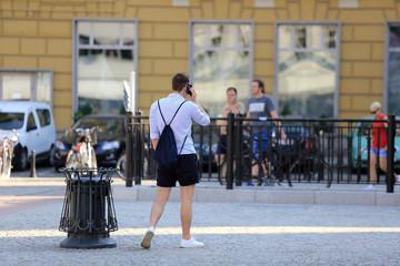 Obraz Młody mężczyzna rozmawia przez telefon w mieście. - fototapety do salonu