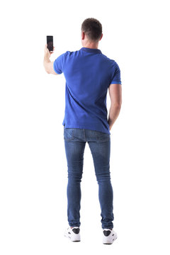Rear view of modern adult casual man taking photo with smart phone. Full body isolated on white background.