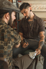 Vintage men tattooing and posing in a retro bar