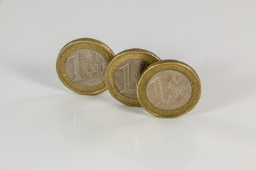Euro coins on white background with reflections