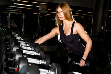 Portrait of fit and sporty brutal athletic young female in fashion sportswear doing exercise with dumbbells. Urban style healthy lifestyle and sport concept. Yoga fitness workout at gym.
