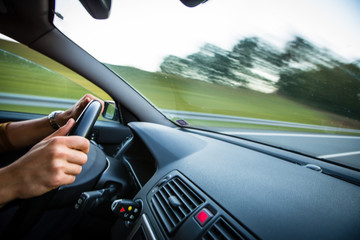 Man driving a car moving fast on a highway (motion blurred image)