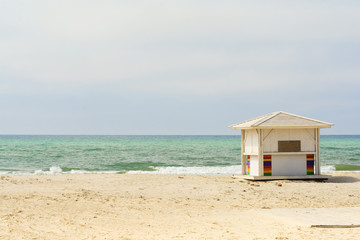 Ocean background. Empty beach. White beach huts next to the sea.