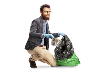 Young guy putting a tin can in a garbage bag