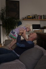 Father playing with his daughter in living room