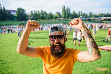 Cheerful fan at summer fest. Man bearded hipster in front of crowd people raise fists green riverside background. Urban event celebration. Hipster in cap happy celebrate event picnic fest or festival