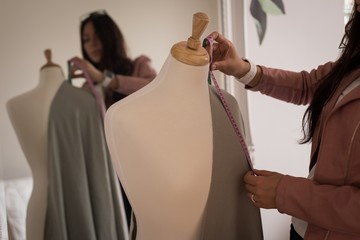 Fashion designer measuring the fabric on dressmakers model