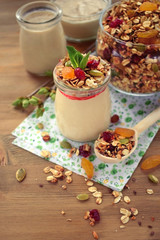 Yogurt topped with granola and mint in a glass jar