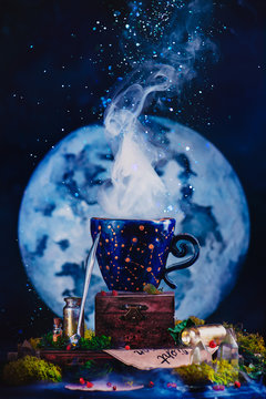 Ceramic cup with constellations in a witch or wizard workplace. Astronomy or astrology still life with Moon, crystals, moss and potion bottles. Magic concept with copy space